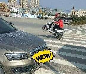一女子在大马路上玩摩托车特技